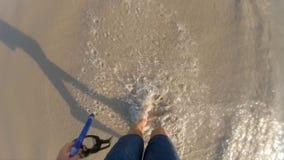 Superslowmotion сняло человека который идет в волны моря держа маску в его руке сток-видео