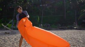 Superslowmotion disparou de um homem novo em uma praia tropical infla um sofá inflável Conceito das f?rias de ver?o vídeos de arquivo