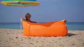 Superslowmotion disparou de uma jovem mulher em uma praia tropical que estabelece em um sofá inflável Conceito das f?rias de ver? video estoque