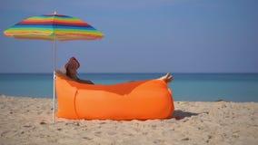 Superslowmotion disparou de uma jovem mulher em uma praia tropical que estabelece em um sofá inflável Conceito das f?rias de ver? filme