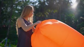 Superslowmotion disparou de uma jovem mulher em uma praia tropical que infla um sofá inflável Conceito das f?rias de ver?o filme