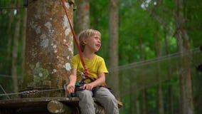 Superslowmotion ha sparato di un ragazzino in un cavo di sicurezza su un itinerario in un parco di avventura della foresta Centro video d archivio