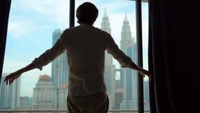 Superslowmotion przegapia miasto strzelał sylwetka pomyślny bogaty człowiek otwiera zasłony okno zdjęcie wideo