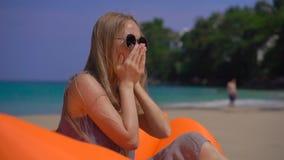Superslowmotion schoss von einer jungen hustenden Frau beim Sitzen auf einem aufblasbaren Sofa auf einem tropischen Strand Reisek stock footage
