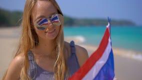 Superslowmotion schoss von einer schönen jungen Frau, die das Tragen reflektierende Sonnenbrille eine Staatsflagge von Thailand h stock footage