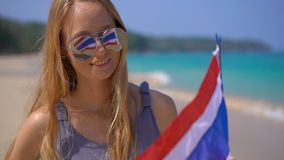 Superslowmotion shot of a beautiful young woman wearing a reflective sunglasses holds a national flag of Thailand. Standing on a beach stock footage