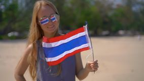 Superslowmotion shot of a beautiful young woman wearing a reflective sunglasses holds a national flag of Thailand. Standing on a beach stock video