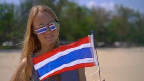 Superslowmotion shot of a beautiful young woman wearing a reflective sunglasses holds a national flag of Thailand. Standing on a beach stock video footage