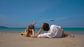 Superslowmotion shot of a happy man and woman tourists laying on a beautifull beach watching a landing airplane stock video footage