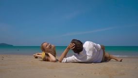 Superslowmotion shot of a happy man and woman tourists laying on a beautifull beach watching a landing airplane stock footage