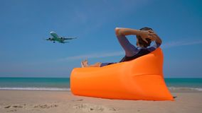 Superslowmotion shot of happy tourist laying on an inflatable sofa on a tropical beach watching an airplane landing.  stock video footage