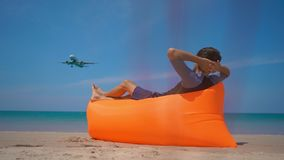 Superslowmotion shot of happy tourist laying on an inflatable sofa on a tropical beach watching an airplane landing.  stock video