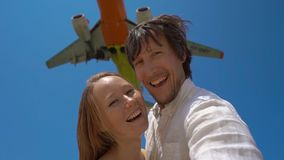 Superslowmotion shot of a happy tourists have fun on a tropical beach with an airplane flying over them.  stock video footage