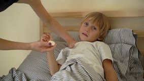 Superslowmotion shot of a sick little boy in a bed. Mother rubs boy`s chest with ointment with essential oils. Baby flu stock footage