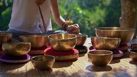 Superslowmotion shot of a woman master of Asian sacred medicine performs Tibetan bowls healing ritual. Meditation with