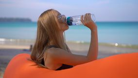 Superslowmotion shot of a young woman on a tropical beach sits on an inflatable sofa and drinks water from a multi. Useable plastic bottle. Drink more water stock video footage