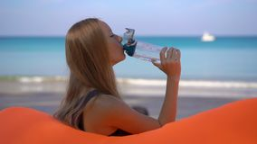 Superslowmotion shot of a young woman on a tropical beach sits on an inflatable sofa and drinks water from a multi. Useable plastic bottle. Drink more water stock video