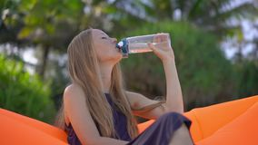 Superslowmotion shot of a young woman on a tropical beach sits on an inflatable sofa and drinks water from a multi. Useable plastic bottle. Drink more water stock footage