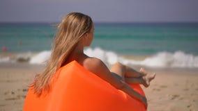 Superslowmotion strzał młoda kobieta relaksuje na inflateble kanapie na tropikalnej plaży zdjęcie wideo