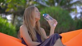 Superslowmotion strzał młoda kobieta na tropikalnej plaży siedzi na nadmuchiwanej napój wodzie od wielo- i kanapie zbiory
