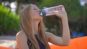 Superslowmotion strzał młoda kobieta na tropikalnej plaży siedzi na nadmuchiwanej napój wodzie od wielo- i kanapie zdjęcie wideo