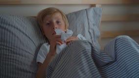 Superslowmotion a tiré d'un garçon qui essuie sa morve avec une serviette Petit garçon malade dans un lit Concept de grippe de bé banque de vidéos