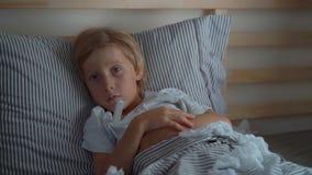 Superslowmotion a tiré d'un petit garçon malade avec un thermomètre dans un lit Concept de grippe de bébé banque de vidéos