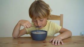 Superslowmotion a tiré d'un petit garçon mangeant un bol de smoothie de banane avec le fruit du dragon, mangue, granola, raisin s clips vidéos