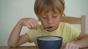 Superslowmotion a tiré d'un petit garçon mangeant un bol de smoothie de banane avec le fruit du dragon, mangue, granola, raisin s banque de vidéos