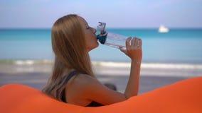 Superslowmotion tiró de una mujer joven en una playa tropical se sienta en un sofá inflable y bebe el agua de un multi almacen de video