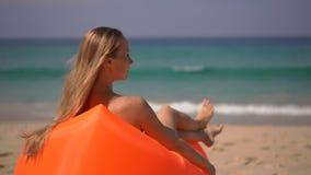Superslowmotion tiró de una mujer joven que se relajaba en un sofá inflateble en una playa tropical almacen de metraje de vídeo
