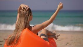 Superslowmotion van een jonge vrouw wordt geschoten die op een inflateble bank op een tropisch strand ontspannen dat stock footage