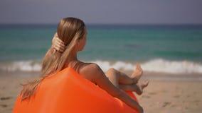 Superslowmotion van een jonge vrouw wordt geschoten die op een inflateble bank op een tropisch strand ontspannen dat stock videobeelden