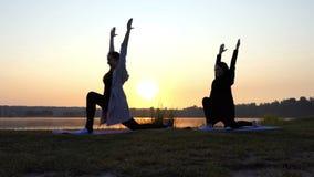 Supersonnenuntergang und Frauen, die Yoga-Übung des Kriegers-2 auf einer See-Bank tun stock video footage