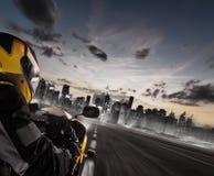 Supersport朝向对现代城市地平线的摩托车车手 免版税图库摄影