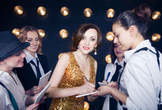 Superstar crowded by paparazzi. Superstar women wearing golden shining dress crowded by paparazzi royalty free stock photo