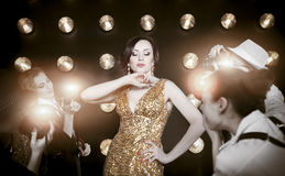 Superstar woman posing to paparazzi. Superstar women wearing golden shining dress posing to paparazzi Royalty Free Stock Images