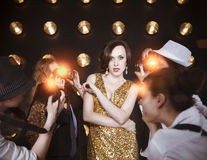 Superstar woman posing to paparazzi. Superstar women wearing golden shining dress posing to paparazzi Royalty Free Stock Photography