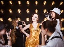 Superstar woman posing to paparazzi. Superstar women wearing golden shining dress posing to paparazzi Stock Image