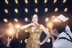 Superstar woman posing to paparazzi. Superstar women wearing golden shining dress posing to paparazzi Royalty Free Stock Image