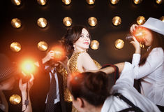Superstar woman posing to paparazzi. Superstar women wearing golden shining dress posing to paparazzi Stock Photos