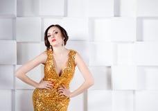 Superstar woman wearing golden shining dress Stock Photo