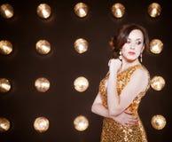 Superstar woman wearing golden shining dress Stock Photos