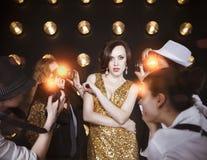 Superstarfrau, die zu den Paparazzi aufwirft Lizenzfreie Stockfotografie