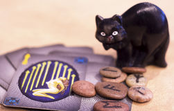 Superstition. Halloween scene tarot cards, northern runes and black cat. Concept of superstition, spells and magic Royalty Free Stock Photo