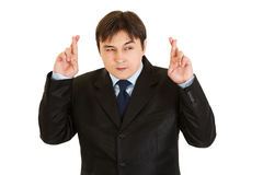 Superstitious businessman holding crossed fingers. Superstitious young businessman holding crossed fingers isolated on white Royalty Free Stock Photos