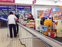 Superstore or supermarket checkout. A checkout in a supermarket or superstore. Customers loading their food into a cart. This is in the Sainsbury store in Royalty Free Stock Photography