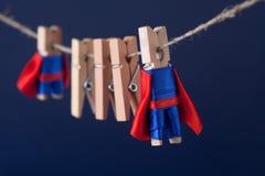 Superteamkonzeptfoto mit Wäscheklammersuperhelden in der blauen Klage und im roten Kap Große kleine starke Helden dunkel lizenzfreies stockbild