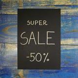 Supertext des verkaufs -50% auf schwarzer Karte Stockfotografie
