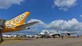 Supertunnel-bohrwagen Qatar Airwayss A380 hinter Scoot Boeing 787 Dreamliner in Singapur Airshow Lizenzfreie Stockbilder